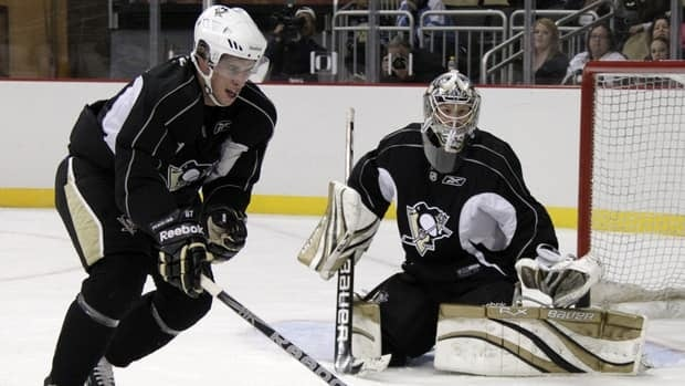 Pittsburgh Penguins' Sidney Crosby, left, skates during a drill with goalie Brad Thiessen during the first day of NHL hockey training camp at the Consol Energy Center in Pittsburgh on Sept. 17.