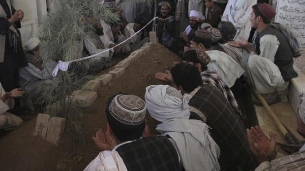 Afghan people offer prayers at the grave of Ahmed Wali Karzai, Afghan President Hamid Karzai's slain half-brother, at his funeral in his family's ancestral village of Karz, in Kandahar province, Afghanistan, on Wednesday.