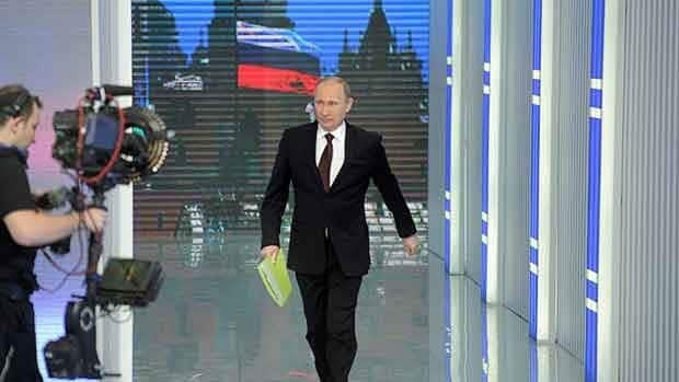 Russian Prime Minister Vladimir Putin enters the hall for a national call-in TV show in Moscow Thursday.