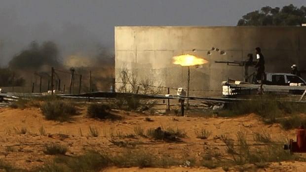 Anti-Gaddafi fighter fires a heavy machine gun outside of Sirte, Gadhafi's hometown.