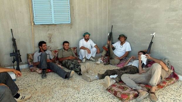 Rebel fighters from the Tripoli Brigade relax at their base close to the front line near the town of Tiji, western Libya, Monday. The rebel fighters of the Tripoli Brigade have a single purpose - to be among the first to enter the Libyan capital and kick out Moammar Gadhafi and his loyalists, aided by their intimate knowledge of the city.