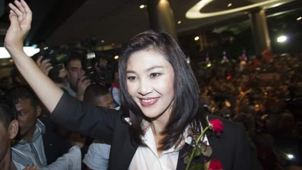 Yingluck Shinawatra comes out to celebrate with her supporters at the Pue Thai Party headquarters Sunday in Bangkok.