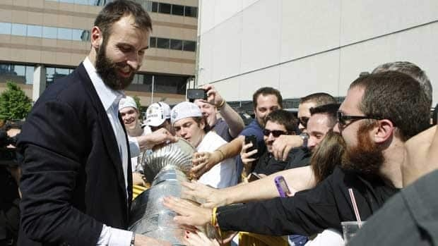 Bruins captain Zdeno Chara, left, lets fans touch the Stanley Cup upon the team's return to Boston on Thursday morning.