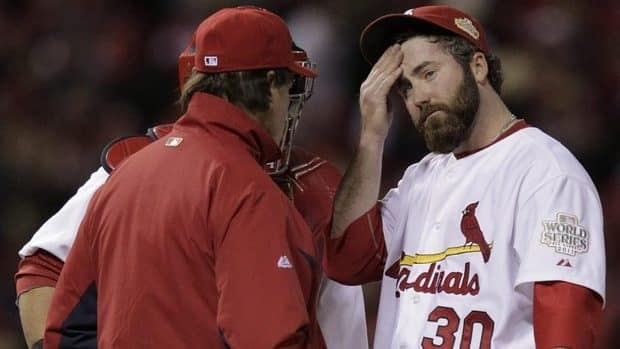 St. Louis Cardinals relief pitcher Jason Motte, right, reacts as manager Tony La Russa takes him out of the game during the ninth inning of Game 2 on Thursday night.