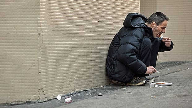 A homeless man eats breakfast on the street in Vancouver. The gap between rich and poor people in Canada is widening, the OECD says.