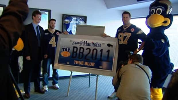 Bombers brass, players, and mascots unveil the new licence plate on Thursday.