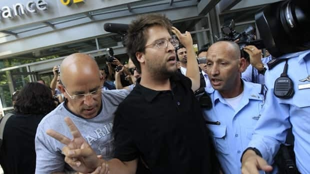 Israeli police officers remove a pro-Palestinian Israeli activist from Ben Gurion International Airport.