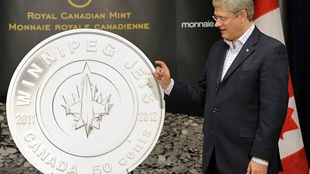 Prime Minister Stephen Harper unveils the new Winnipeg Jets 50 cent coin before Sunday's first NHL home hockey game of the Jets against the Montreal Canadiens in Winnipeg.