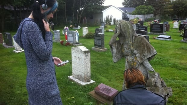 Nicole Tremblay and Rosaling Hennigar take readings at the site of the witch's grave in Charlottetown.