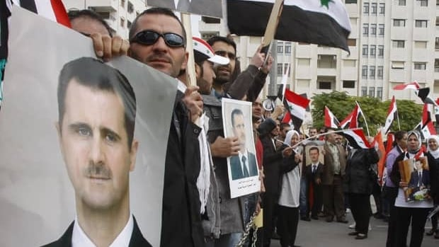 Pro-Syrian regime protesters hold portraits of Syrian President Bashar Assad and shout slogans against the Arab League, as they gather outside the Syrian Foreign Ministry in Damascus on Monday.