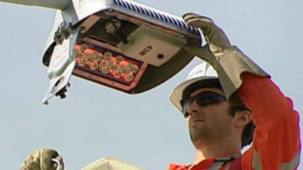 A worker converts an Edmonton streetlight from a traditional bulb to LED.