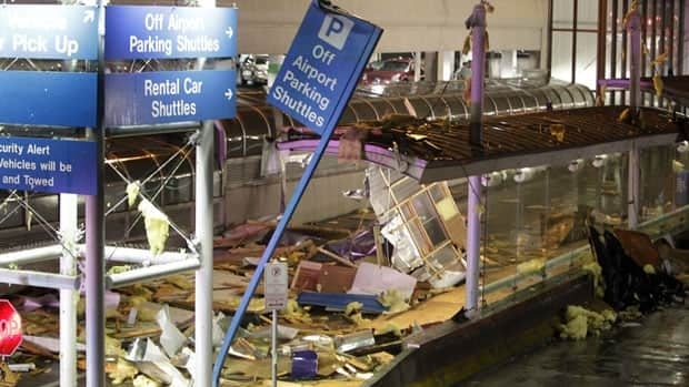 Storm damage is seen next to a parking garage outside terminal one at St. Louis International Airport on Friday.