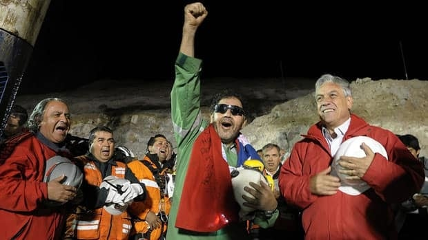The last miner to be rescued, Luis Urzua, centre, gestures as Chile's President Sebastian Pinera, right, looks on on Oct. 13, 2010. The story of the 69-day ordeal of the 33 miners is to be adapted for the screen.