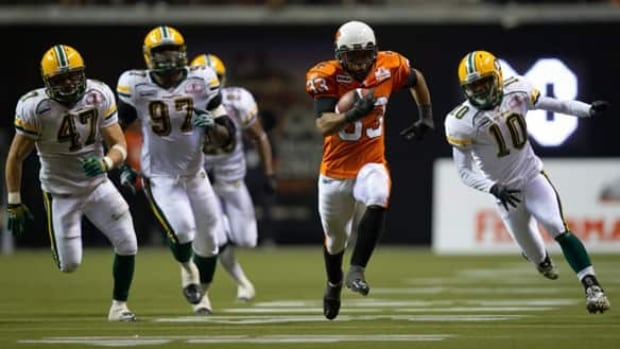 B.C. Lions' Andrew Harris, centre, outruns Edmonton Eskimos' JC Sherritt, from left, Julius Williams and Donovan Alexander for a 63-yard-touchdown during the second half on Friday night.