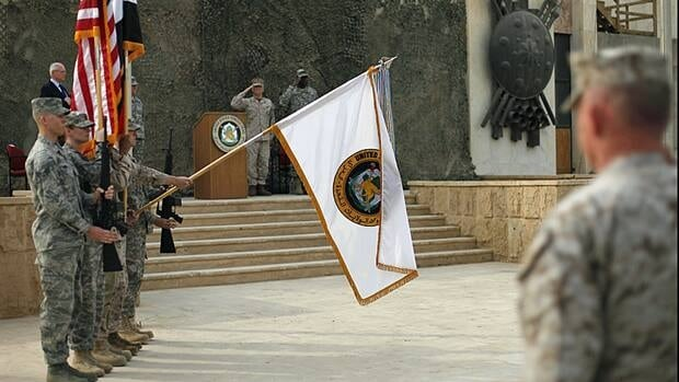 US Forces Iraq flags are lowered before being encased during ceremonies in Baghdad on Thursday. The ceremonies mark the official end of the U.S. military mission in Iraq.