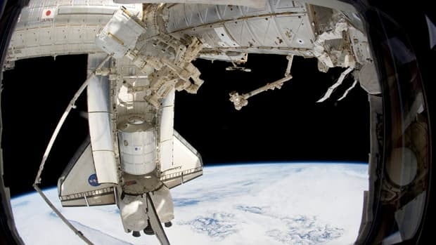 Discovery and the Canadian-built Special Purpose Dextrous Manipulator, are photographed by a crew member on the International Space Station. This is the last time the Shuttle Discovery will dock with the International Space Station.