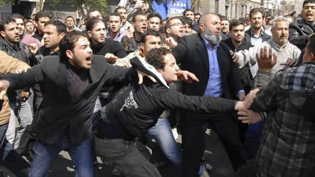 Syrian supporters and opponents of President Bashar Assad clash after Friday prayers in Damascus.