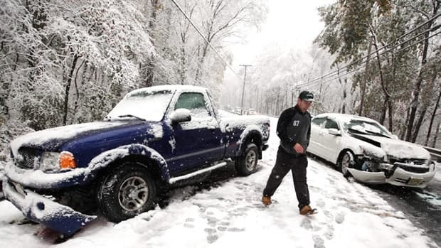 A man walks by a two-vehicle accident in New Jersey on Oct. 29, 2011. As much as 40 centimetres of snow fell in the state as a winter storm walloped the U.S. Eastern Seaboard.