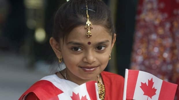 Shahnaz Begum smiles and waves Canadian flags as she enjoys the annual Canada Day celebrations in Montreal,  July 1, dressed in traditional South Asian garb.