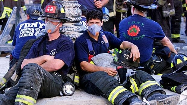 New York City firefighters take a break on West Street near the wreckage of the World Trade Center on  September 12, 2001.