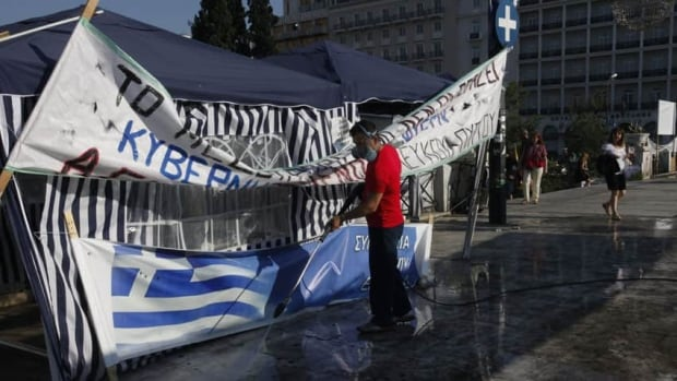 Workers clean up debris from two days of protests in Syntagma Square in central Athens as Greek lawmakers pass austerity measures demanded by creditors.