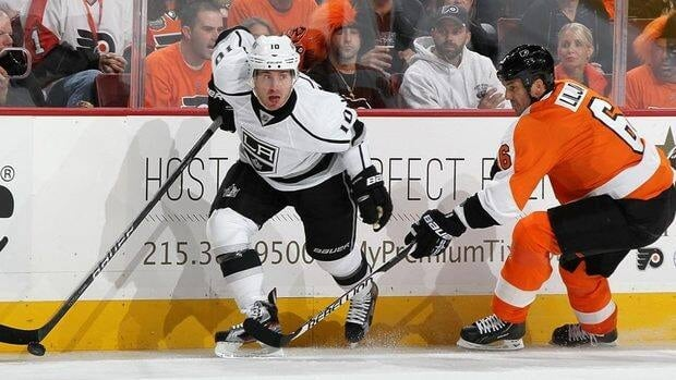 Kings' Mike Richards, left, controls the puck against Andreas Lilja of the Philadelphia Flyers.