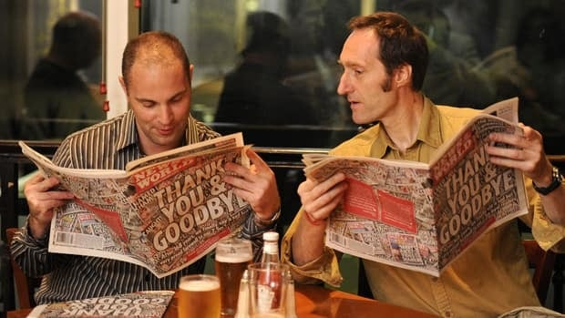 Men look at the last edition of The News of The World newspaper in the bar where many of the journalists from the newspaper gathered after the closure of the newspaper.