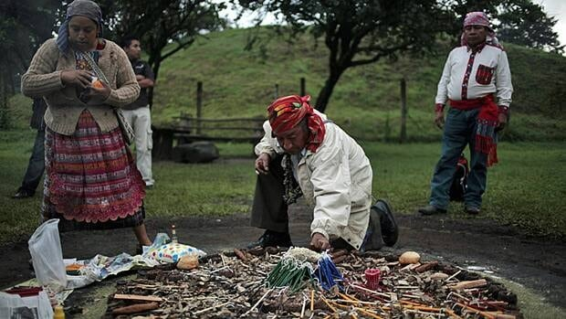 People prepare the sacred fire with candles, bread and honey during the Maya Tz'ikin, or the Day of the Birds ceremony, in the Kaminal Juyu archeological zone in Guatemala City. The ceremony is one of another forty leading up to the end of the current Mayan calendar cycle of 5026 years, which ends on December 21, 2012.