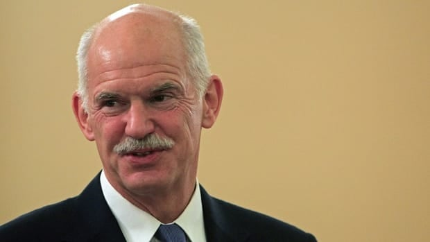 Greek Prime Minister George Papandreou laughs during a ceremony at the presidential palace in Athens on Wednesday, before his teleconference with the leaders of France and Germany.