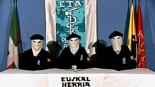 A video frame from 2006 shows three members of the Basque separatist group ETA seated at a table in front of an ETA flag with a Basque Country symbol in foreground. ETA issued a statement Thursday announcing an end to its violent independence campaign.