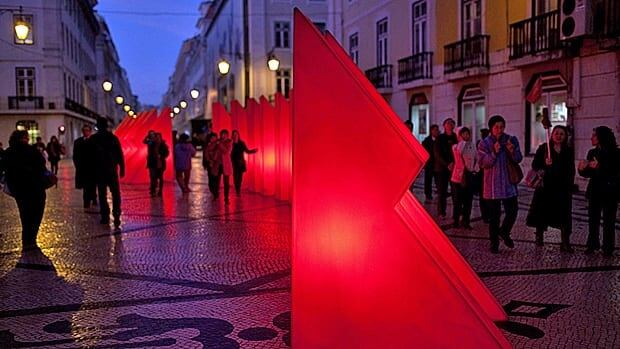 Pedestrians walk around Christmas decorations in on the Rua Augusta, Lisbon's main shopping street. This year the city has put on a somber show that matches the somber mood of austerity.