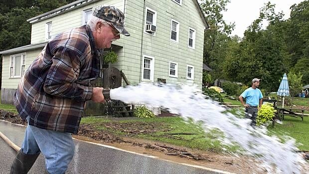 Michael Groff pumps the water out of the basement of his home in York, Pa., on September 8.