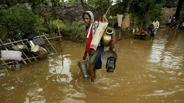 An Indian woman returns to her village through flood waters at Rasulpur village in Orissa's Jajpur district on Sunday. Since the monsoon began in August more than 70 people have died in Orissa.