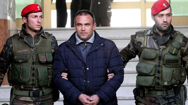 A man identified as Francesco Maisano, an alleged crime boss, is escorted by Italian Carabinieri paramilitary police officers soon after his arrest in southern Italy Tuesday as part of a crackdown against the 'ndrangheta crime syndicate.