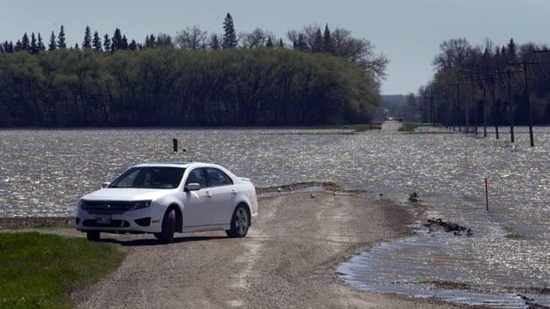 A car turns around as the waters from the Assiniboine River breach flood across a road on May 17 near Newton. The dike was intentionally breached to relieve pressure from the rising river.