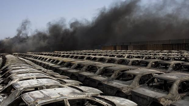 Burned cars are seen next a plume of black smoke in the port of Misrata, Libya, on Wednesday, following a fierce bombardment by government forces.