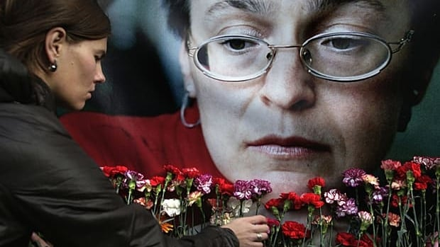 A woman places flowers at a portrait of slain journalist Anna Politkovskaya, during a rally in downtown Moscow, Wednesday, Oct. 7, 2009. Hundreds of people rallied Wednesday on the third anniversary of the killing of Anna Politkovskaya, calling on the authorities to find and punish the killers of journalists and human rights activists in Russia.