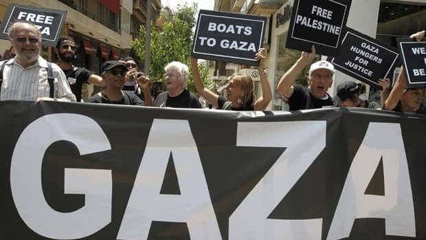 U.S. activists chant slogans after a news conference about an international flotilla to blockaded Gaza, in Athens, Monday. Organizers say Israel is pressuring Greece to halt the ships' departure.