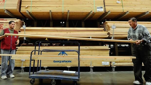 A Lowe's employee helps a customer with a lumber purchase in Burbank, Ca., in April. A tepid new housing market in the U.S. continues to hold down Canadian export lumber prices.