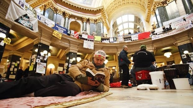On his third straight night of sleeping at the capitol building in Madison, Wis., Xavier Leplae reads. He and other opponents of Gov. Scott Walker's bill to eliminate collective bargaining rights for many state workers were ordered to leave the building Thursday night.