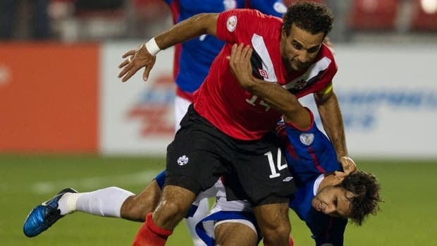 Canada's Dwayne De Rosario, front, takes down Puerto Rico's Andres Perez during the second half of World Cup qualifying action Tuesday in Toronto.