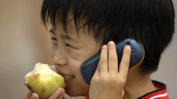 A boy speaks on a mobile phone in Bejing's Tiananmen Square. Some countries have started advising their citizens to limit children's exposure to cellphone radiation.