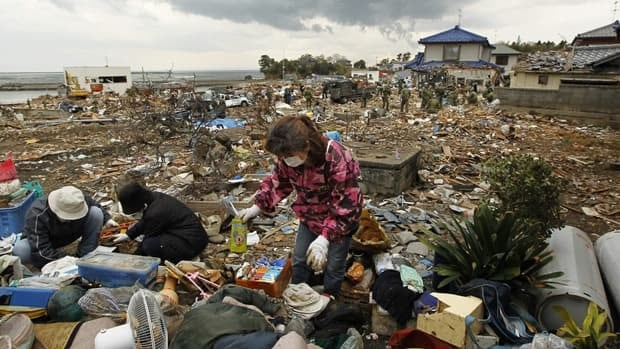 Shichigahamamachi residents look for their neighbours' usable belongings at Shobudahama fishery port Monday as Japan Ground Self-Defense Force members search for missing people in their third major recovery operation since the March 11 earthquake.