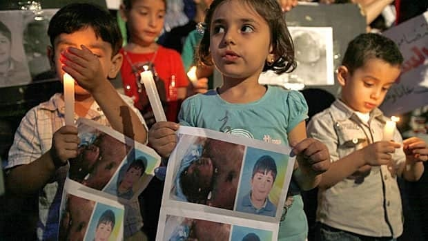 Syrian children carry pictures of 13-year-old Hamza al-Khatib during a protest in front of the United Nations building in Beirut on Wednesday. The boy, who activists say was tortured and killed by security forces, has become a symbol in protests against Syrian President Bashar al-Assad.