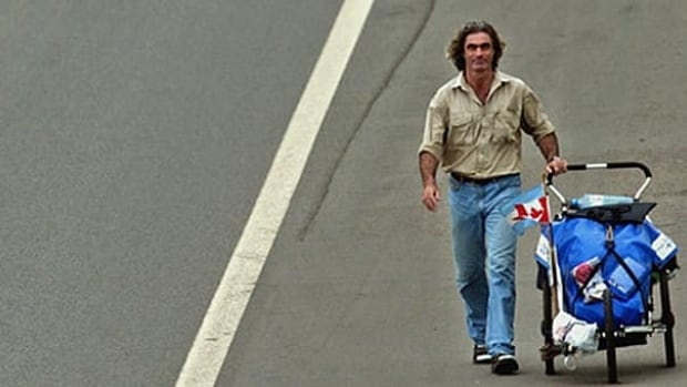Round-the-world walker Jean Béliveau, shown walking in Lujan, Argentina, in 2003, carried everything he needed in a three-wheeled stroller.