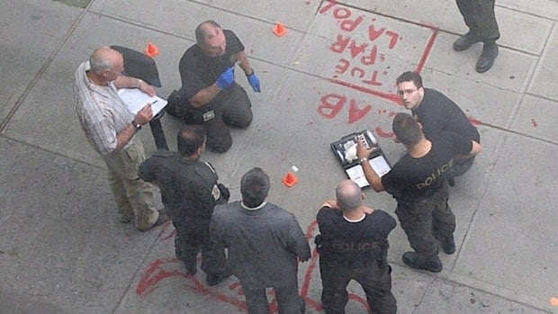 Provincial police on Thursday reconstruct the incident on a sidewalk bearing graffiti left by protesters Wednesday night.