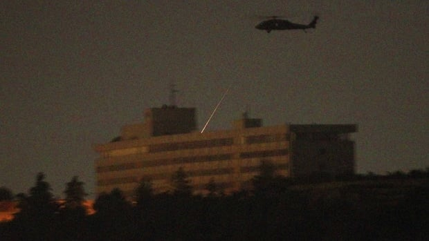 A NATO helicopter fires a missile on the roof of the Intercontinental hotel in Kabul early Wednesday.