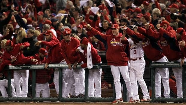 The St. Louis Cardinals bench celebrates after Lance Berkman hit a game-tying RBI single in the 10th inning during Game 6 on Thursday night.