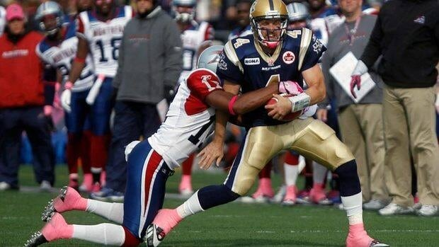Winnipeg Blue Bombers Buck Pierce, right, is tackled by Montreal Alouettes' Chip Cox during the first half Saturday in Winnipeg.