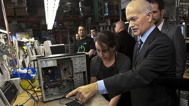 NDP Leader Jack Layton talks with a technician at a computer recycling operation during a campaign stop in Montreal on Thursday, March 31, 2011. The federal election will be held on May 2.